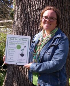 Marie Fidoe proudly displays her Green Level certification sign. Photo: C Junck